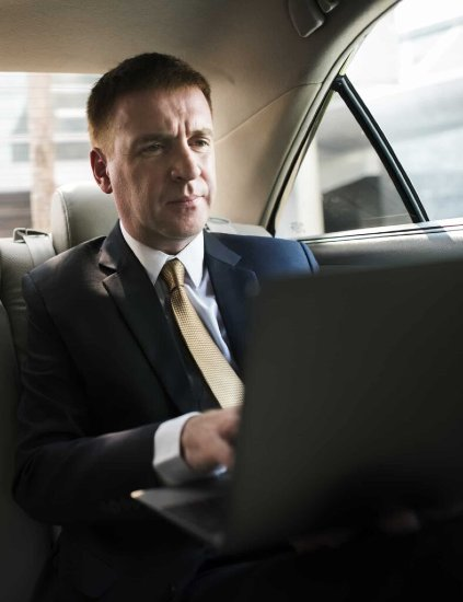 businessman-inside-a-car-working-on-his-laptop